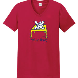"Red t-shirt with a line-art design (navy blue strokes with white and yellow fill) on the chest of the shirt. The art depicts a white dog crouching on a yellow table. The words ""Be Dog Happy"" are in navy blue across the bottom of the design."